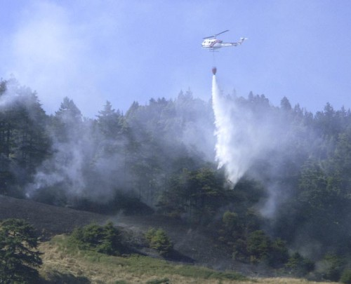 A Cal Fire helicopter battles a wildfire on the Lost Coast